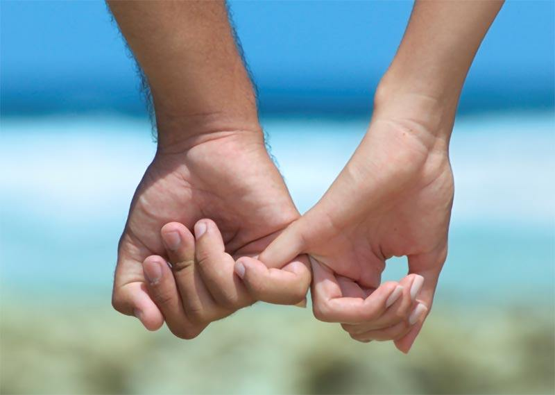 Man and woman holding pinky fingers on beach
